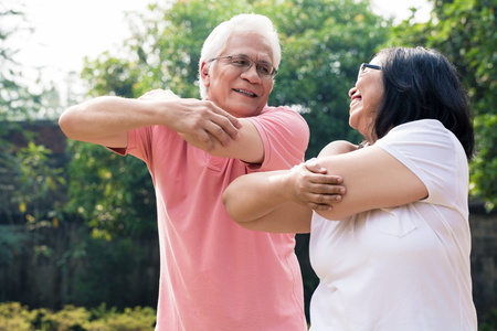 Senior man assisting his wife during warming up exercises for the upper body outdoors in summer