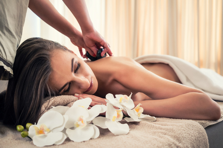 pain: Young woman lying down while receiving hot stone massage at Asian spa and wellness center Stock Photo