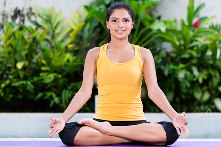 gyan: Young woman practicing yoga in lotus position for meditation and physical stability Stock Photo