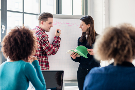 educational problem solving: Involved students sharing ideas and opinions while brainstorming during an interactive class in the classroom of a modern college or university