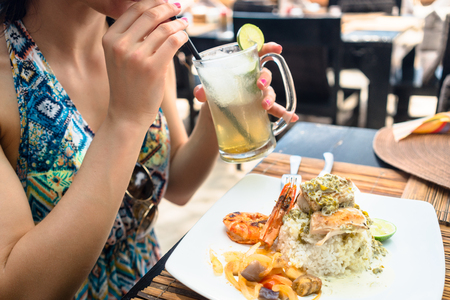 Woman guest eating seafood and drinking cocktail in restaurant Stock Photo