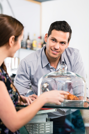 cup: Friendly waiter offering to young female customer fresh French croissants for breakfast Stock Photo