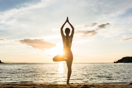 asana: Full length rear view of the silhouette of a woman standing on one leg while practicing the tree yoga pose on a tranquil beach, shot at sunset during summer vacation in Indonesia