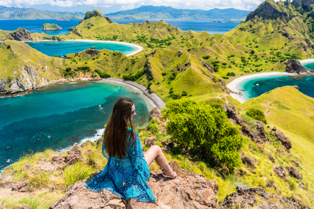 Rear view of a young woman enjoying the awesome view of Padar Island while sitting on the top of a volcanic mountain, during summer vacation in Indonesia