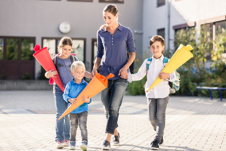 Mum and children with paper funnels for candy after first day at school
