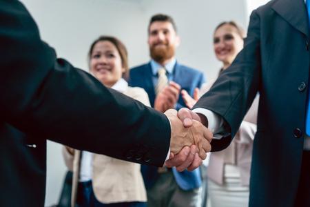 3 명의 직원의 박수에 두 비즈니스 남자의 악수에 근접 회사의 성공에 대한 중요한 합의 후 스톡 콘텐츠