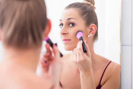 bathroom tiles: Woman powdering her face with cosmetic brush in front of bathroom mirror