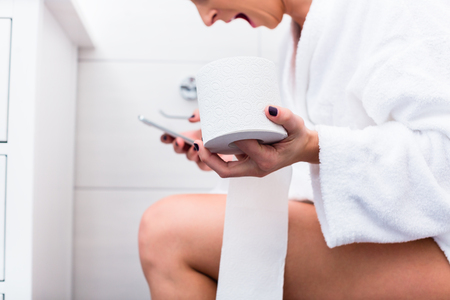 Woman in bathroom sitting on toilet writing text message on cell phone