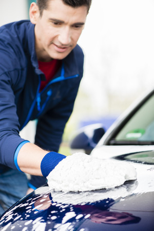 microfiber: Hard-working young man polishing car with white microfiber mitt at auto wash