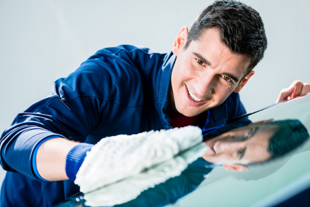 mitt: Cheerful young male worker polishing car with white soft microfiber mitt at auto wash