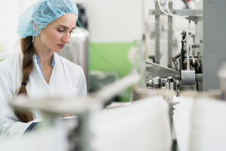Happy female employee wearing protective headwear and white lab coat while working as a manufacturing engineer in a contemporary cosmetics factory