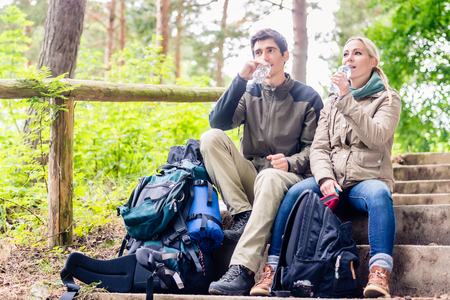 Backpackers hiking and taking rest in the woods and having mineral water Stock Photo
