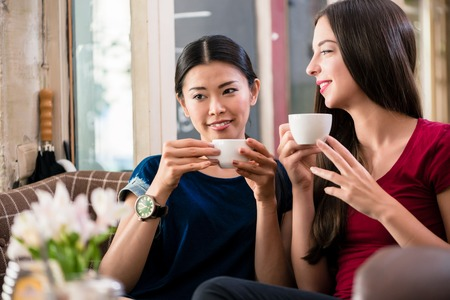 Young Asian woman daydreaming while drinking a cup of coffee with her best friend
