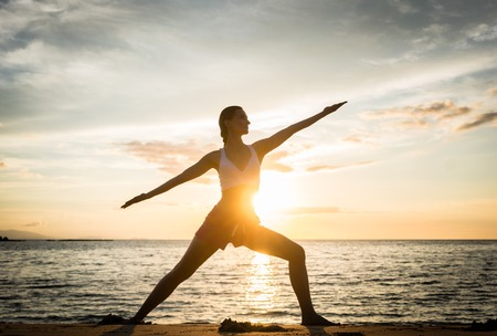 Full length side view of the silhouette of a fit woman practicing the warrior yoga pose against sky at sunset during summer vacation in Flores Island, Indonesia Stock Photo