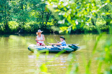 Couple in boat on pond or lake fishing, woman with angle and man is steering