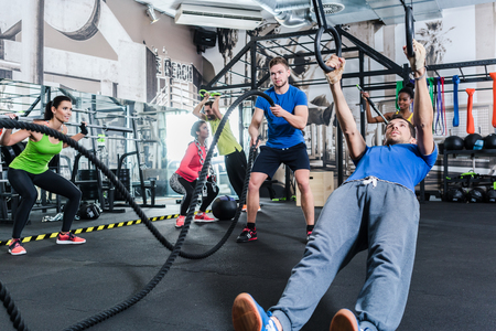 Men and women at functional fitness training in gym doing sport on rings and rope Stock Photo