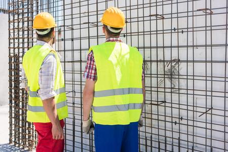 Zwei Angestellte, die Sicherheitsausrüstung tragen, während sie die Haltbarkeit der Stahlkonstruktion für die Verstärkung der Wände eines im Bau befindlichen Gebäudes überprüfen