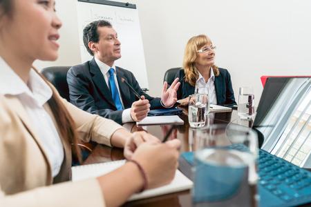 Hombres y mujeres altos directivos sentado durante una reunión interactiva importante en la sala de conferencias de una corporación exitosa Foto de archivo