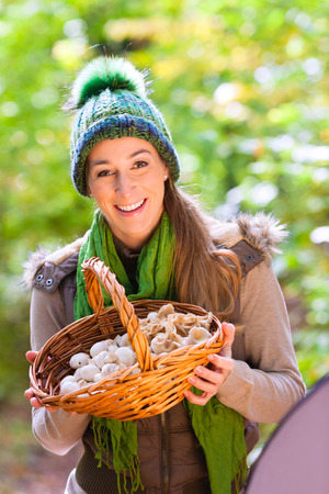 Woman with basket full of champignons in forest Stock Photo