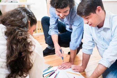 Architekten oder Bauingenieure bauen über Baupläne auf dem Büroboden Standard-Bild