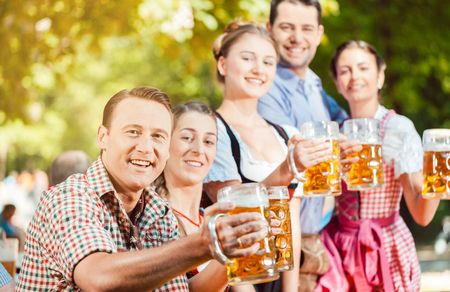 In Beer garden - friends in Tracht, Dirndl and Lederhosen drinking a fresh beer in Bavaria, Germany Stock Photo - 84710489