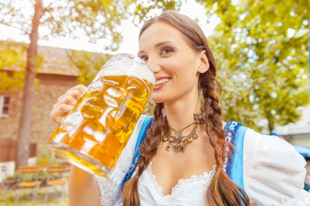 Woman wearing Dirndl is drinking beer in a Bavarian beer garden
