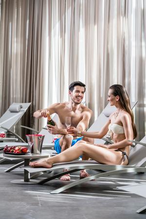 Romantico giovane che apre una bottiglia di champagne mentre si rilassa con il suo compagno in piscina in un hotel di lusso