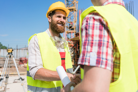 Cheerful construction worker shaking the hand of an architect or a foreman as a gesture of agreement, and partnership at the beginning of a new project Stock Photo