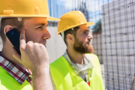 Zijaanzichtclose-up van een arbeider die gele bouwvakker dragen terwijl het spreken op mobiele telefoon tijdens het werk, op de bouwwerf van een lopend gebouw Stockfoto