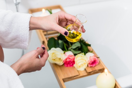 Woman preparing wellness bath with flowers, candles and fragrance oil in tub Stock Photo