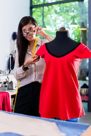 Asian tailor adjusts garment design on mannequin in her workshop Stock Photo