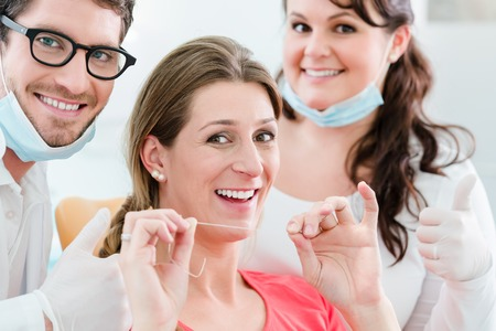 prophylaxis: Woman at dentist using dental floss, the doctor explaining proper use Stock Photo