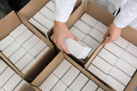 High-angle close-up view of the hands of a manufacturing worker putting packed products, in cardboard boxes before export or shipping during manual work in a cosmetics factory