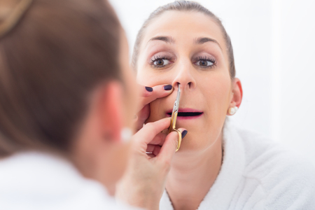 Young Woman in bathroom cutting her nostril hair