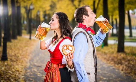 pretzel: Woman and man from Austria or Bavaria standing back-to-back and drinking beer