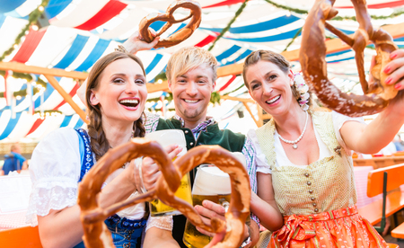 Three friends in beer tent at Dult or Oktoberfest holding giant pretzels up in the air Foto de archivo