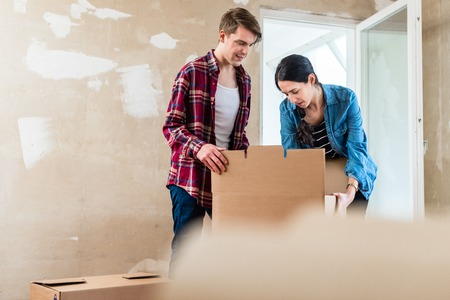 Young woman bringing an open heavy cardboard box while moving in with her boyfriend into their new home