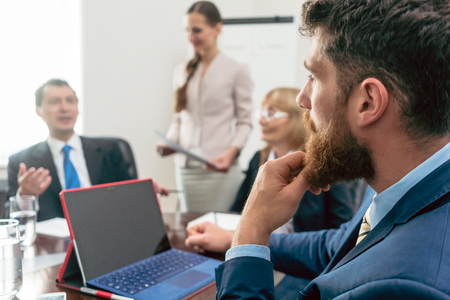 Side view of a pensive business consultant listening to the manager of an important corporation during a problem-solving meeting in the conference room