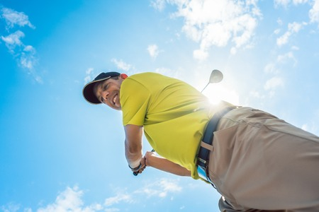 Low-angle view of a professional player wearing golf outfits while holding the club ready for the strike during individual game outdoors against cloudy sky Stock Photo