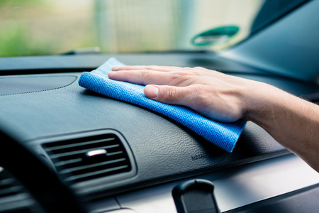 Man wiping the dashboard of his car with an anti-static cloth to remove accumulated dust, close up of his hand