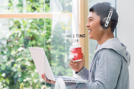 Motivated young employee smiling while holding a cup of coffee and a laptop in the meeting room of a modern company Stock Photo