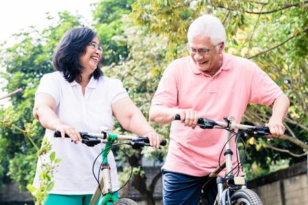portrait de couple âgé actif souriant tout en se tenant sur les vélos en plein air en été