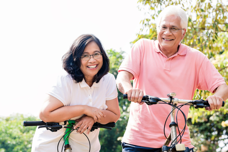 Portrait of active senior couple smiling while standing on bicycles outdoors in summer Banco de Imagens