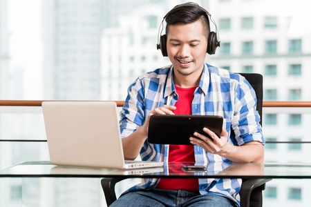 Young asian man having video conference in skyscraper office Stock Photo