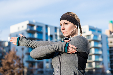 Portrait of a determined young woman stretching her left arm during warm-up routine before outdoor workout in a sunny day Stock Photo