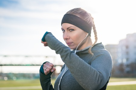 Portrait of a strong young woman practicing boxing exercise while looking forward with confidence and determination outdoors in the city Standard-Bild