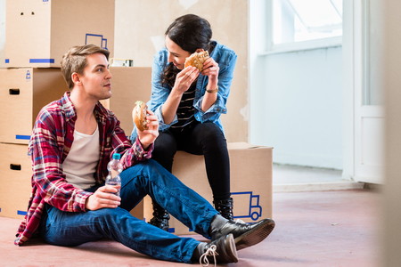 Young couple looking tired while eating a sandwich during break from renovation in the interior of their new home