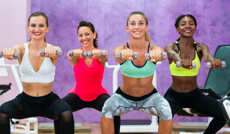 Beautiful athletic women doing squats while holding dumbbells with straight arms forward during functional training group class in a modern fitness club for ladies only