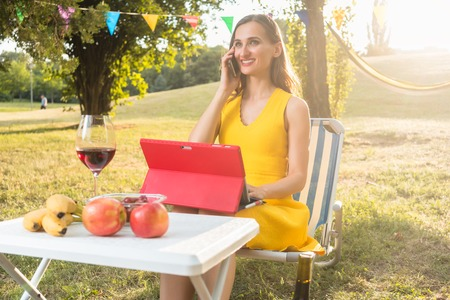 coordinating: Successful and beautiful female entrepreneur managing business through mobile phone and tablet while sitting down on a picnic chair in the park