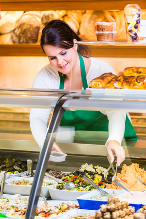 saleslady: Saleswoman in delicatessen selling appetizers and mezze Stock Photo